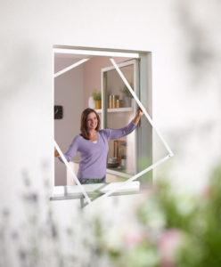 Frau montiert Pollenschutz-Gitter am Fenster